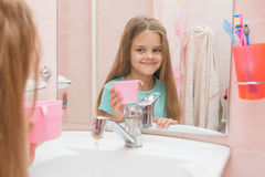 Happy girl holding a cup and looks in the mirror in the bathroom Stock Photos