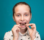 Happy girl holding dental braces. On a blue background Stock Image