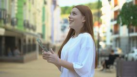 Happy girl holding dollar banknotes in hands, looking at shop windows, plans stock footage