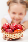 Happy girl holding easter eggs in a basket royalty free stock image