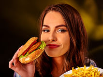Happy girl holding fastfood hamburger and fried potatoes . Fastfood concept fastfood hamburger and fried potatoes on green stock photo