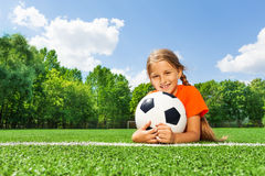 Happy girl holding football with both arms Royalty Free Stock Images