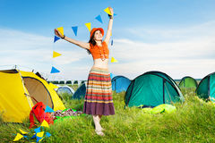 Happy girl holding garland with flags at campsite Royalty Free Stock Photos
