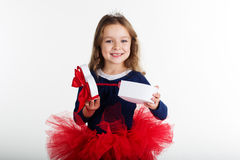 Happy girl is holding gift box with red ribbon Stock Image