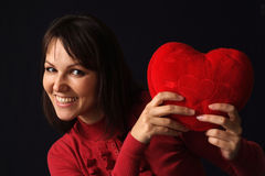 Happy girl holding a heart pillow Stock Photography