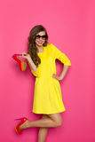 Happy Girl Holding High Heels. Happy young woman in yellow mini dress holding high heels and posing on one leg against pink background. Three quarter length Royalty Free Stock Photography