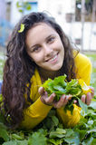 Happy girl holding leafs in the garden Royalty Free Stock Photo