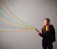 Happy girl holding a phone with colorful abstract lines Royalty Free Stock Photography