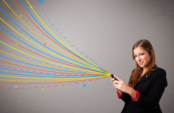 Happy girl holding a phone with colorful abstract lines Royalty Free Stock Images