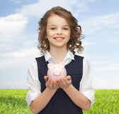 Happy girl holding piggy bank on palms Royalty Free Stock Photos