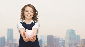 Happy girl holding piggy bank on palms Stock Images
