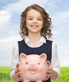Happy girl holding piggy bank. People, money, finances and savings concept - happy girl holding big piggy bank on palms over blue sky and grass background Royalty Free Stock Images