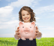 Happy girl holding piggy bank. People, money, finances and savings concept - happy girl holding big piggy bank on palms over blue sky and grass background Stock Photography