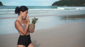 Happy girl holding a pinapple cocktail on a beach stock video