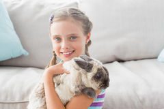 Happy girl holding rabbit in living room Royalty Free Stock Image