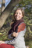 Happy girl holding red autumn leaf in the park Royalty Free Stock Photos
