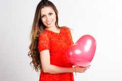 Happy girl holding red heart balloons Stock Photography