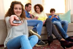 Happy girl holding remote control with family Royalty Free Stock Photos