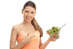Happy girl holding a salad and pointing Stock Photos