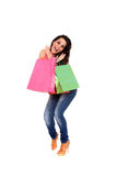 Happy girl holding shopping bags. Happy young girl holding shopping bags isolated on a white background Royalty Free Stock Images