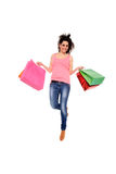 Happy girl holding shopping bags. Happy young girl holding shopping bags jumping isolated on a white background Stock Images