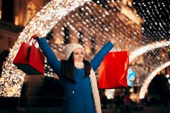 Happy Girl Holding Shopping Bags on Christmas Lights Décor royalty free stock photography
