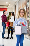 Happy girl holding shopping bags in mall Royalty Free Stock Image
