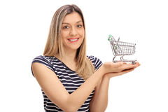 Happy girl holding a small empty shopping cart Royalty Free Stock Images