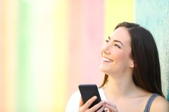 Happy girl holding phone thinking looking at side royalty free stock photography