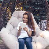Happy girl holding  tablet PC, sitting in a park at summer day Royalty Free Stock Image