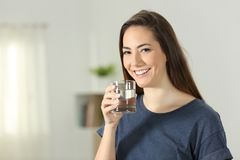 Happy girl holding a transparent glass of water. Standing at home Stock Images