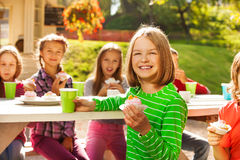 Happy girl holds cupcake with children sitting Stock Photo
