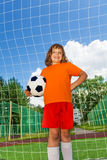 Happy girl holds football standing near white net Stock Photo