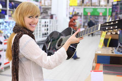 Happy girl holds guitar in supermarket Royalty Free Stock Photography
