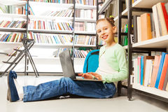 Happy girl holds laptop and sits near bookshelf Royalty Free Stock Images