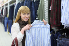Happy girl holds male shirt in shop Stock Photo