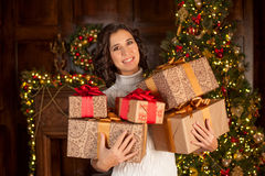 Happy girl holds many Christmas gifts Stock Photography