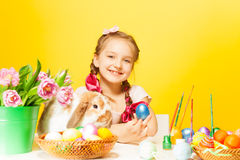 Happy girl holds pail with tulips and rabbit near Royalty Free Stock Images