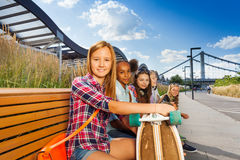 Happy girl holds skateboard on bench with girls Royalty Free Stock Images