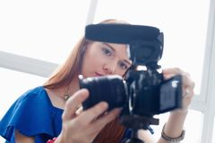 Woman Recording Vlog Video Blog Using DSLR Camera. Happy girl at home setting video camera and attaching lens to dslr. People and technology, young woman working stock photography