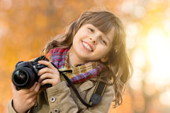 Happy girl. Horizontal photo, happy beautiful little girl with photocamera, autumnal portrait royalty free stock images