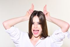 Happy girl with horns gesture on white. Makeup smokey eyes for model with soft skin. Fashion look concept. Beauty and hairdresser. Trendy woman with stylish stock images