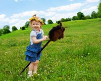Happy girl with horse stick Royalty Free Stock Images