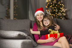 Happy girl hugging sister on sofa during Christmas Royalty Free Stock Image