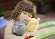 Happy girl hugging toys Stock Images