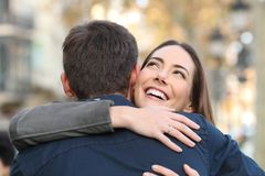 Happy girl hugs her boyfriend in a city street royalty free stock photography