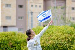 Happy Girl with Israel flag. Image to illustrate election win, patriotic holiday Independence day Israel - Yom Ha`atzmaut and Israeli Memorial Day stock photo