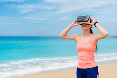 Happy girl jogger wearing VR technology glasses. Happy attractive girl jogger wearing VR technology glasses standing on beach and adjusting device to viewing 3D Royalty Free Stock Photos