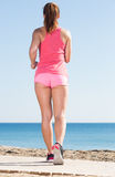 Happy girl jogging at seaside Royalty Free Stock Photography