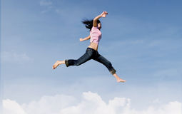 Happy girl jump over clouds Stock Photo